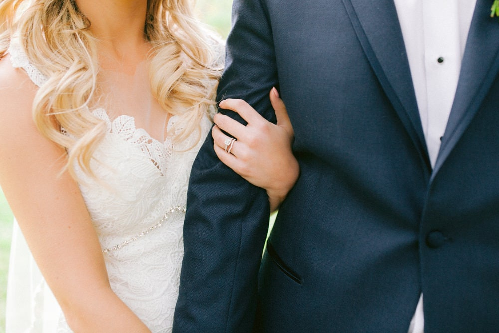 Close up photo of Bride and Groom while Bride holds grooms arm