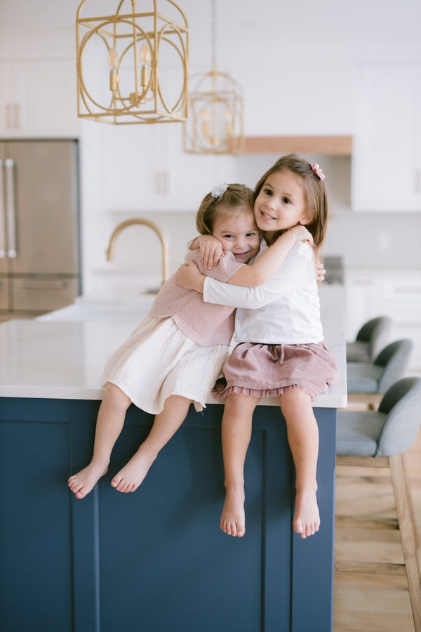 Sisters hugging in kitchen