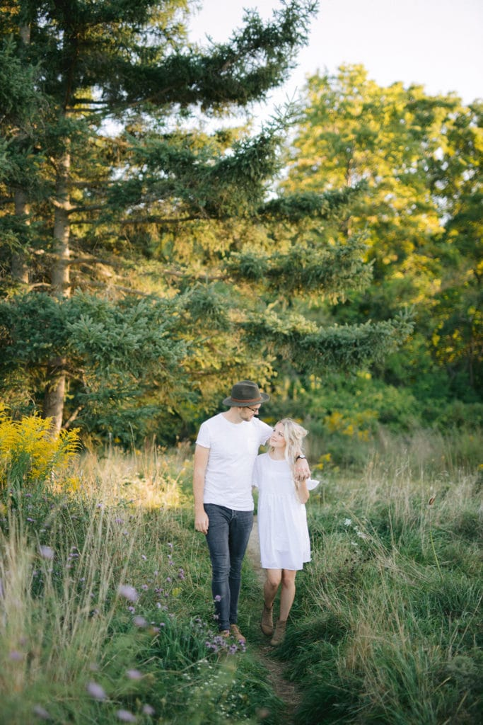 Husband and wife walking together through field