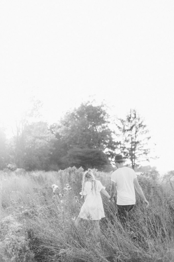 black and white photo of a couple walking and exploring a field of tall grass