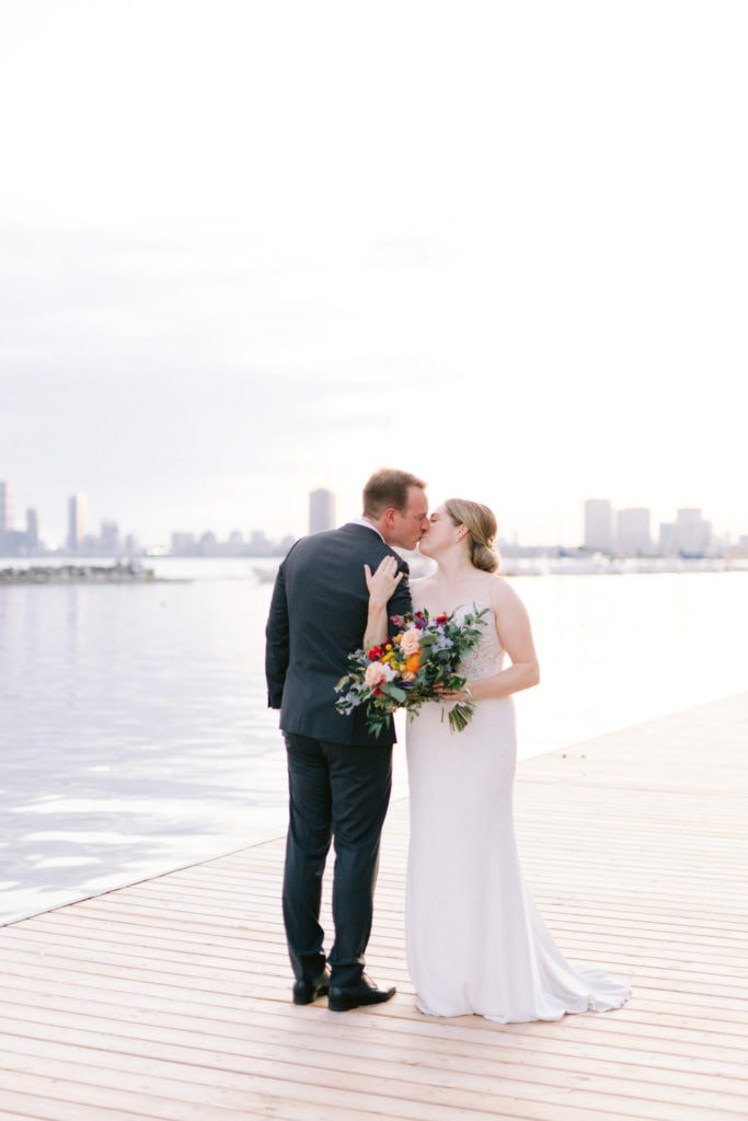 Newly Wed Couple Kissing On A dock at sunset
