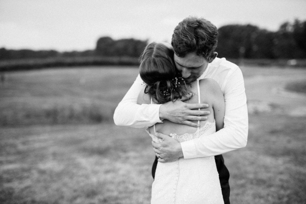 Bride and Groom sharing an emotion hug. Photo is in black and white